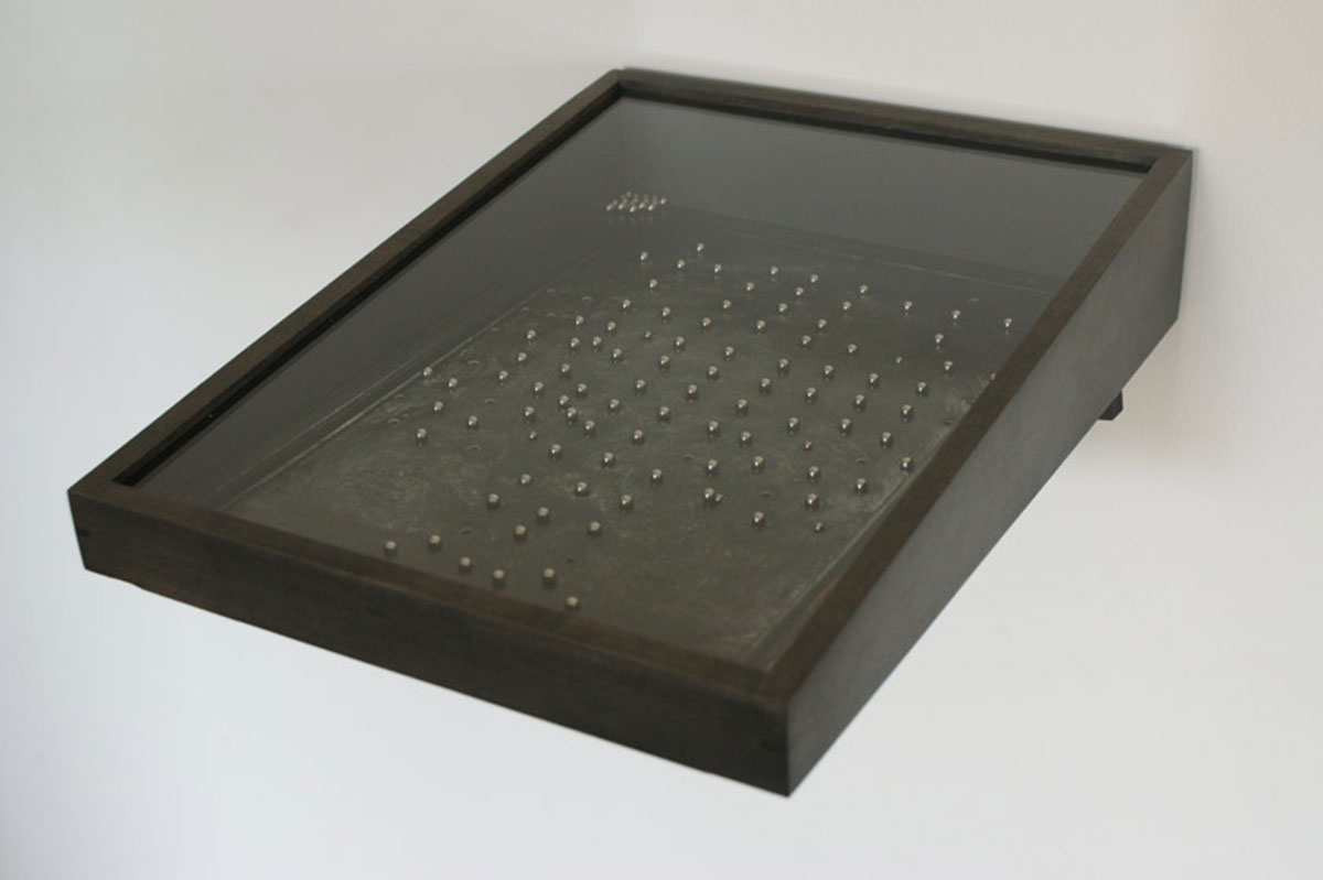Absolution, © 2009 – 10, Perforated c-prints of confessional screens mounted on black cardboard; loose stainless steel balls inside the frame, wooden shelf, Series of 20, each approx. 7 x 35 x 27 cm